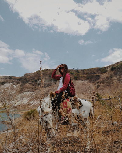 Smiling woman sitting on horse against sky