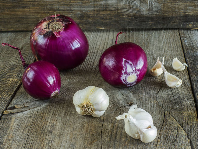 raw red onion and garlick on old weathered wooden background Background Close-up Food Food And Drink Freshness Garlic Bulb Garlick Healthy Eating High Angle View Horizontal Indoors  No People Old Onion Raw Red Table Weathered Wood - Material Wooden