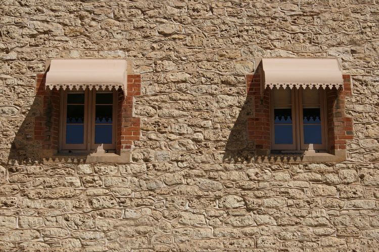 Two shaded windows in a stone wall Shaded Architecture Building Exterior Built Structure Day House No People Outdoors Pair Of Windows Stone Wall Street Photography Street Scene Window