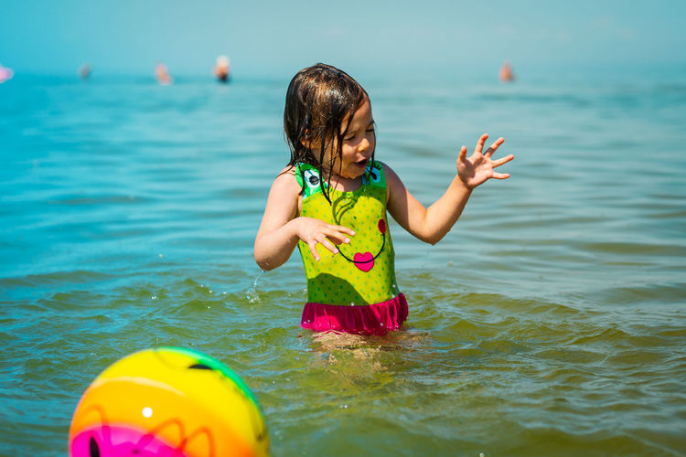Girl playing with ball at beach