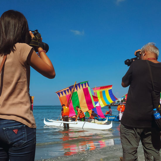 Rear view of people photographing sea against sky