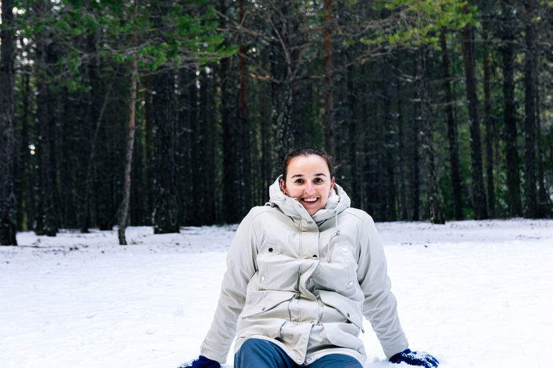 Portrait of smiling woman sitting on snow covered land against trees