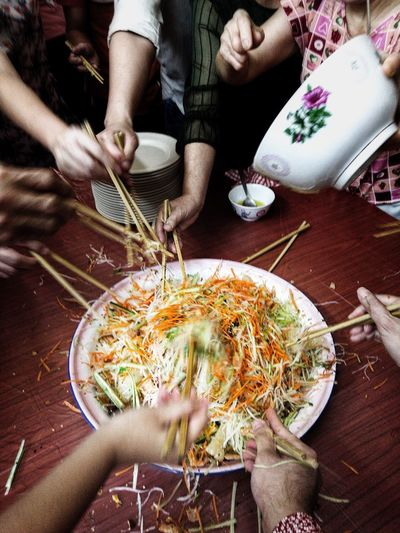 Lou Hei. Customary on the first day of the lunar new year to bring in prosperity (Huat) Asian Culture Lou Hei Lunar New Year Food And Drink Bowl Noodles Food Chopsticks Human Hand Indoors  Chinese Food