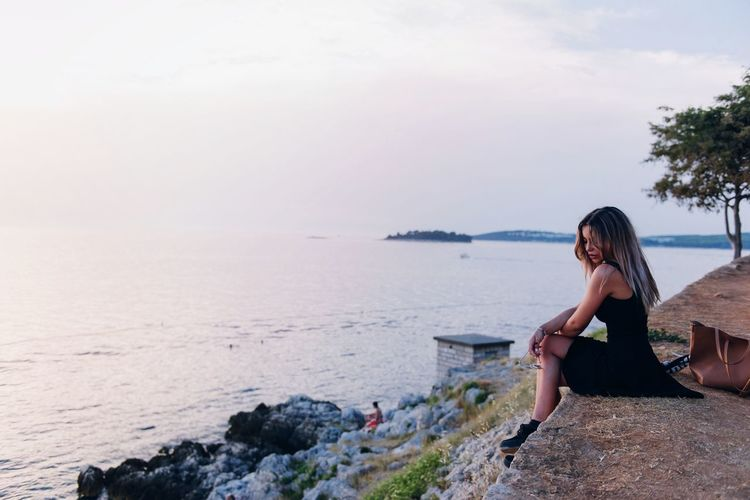 Portrait of young woman standing on rock by sea against sky