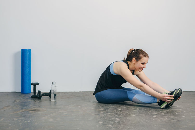 Young woman Stretching after workout in Gym Full Length One Person Indoors  Sitting Lifestyles Real People Copy Space Exercising Healthy Lifestyle Side View Young Adult Flooring Wall - Building Feature Leisure Activity Sports Clothing Women Young Women Relaxation Hairstyle Beautiful Woman Fitness Workout Working Working Out Inside Photography Horizontal Sport Clothes Sport Clothing Athlete