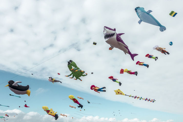 Low Angle View Of Various Colorful Balloons Flying Against Cloudy Sky
