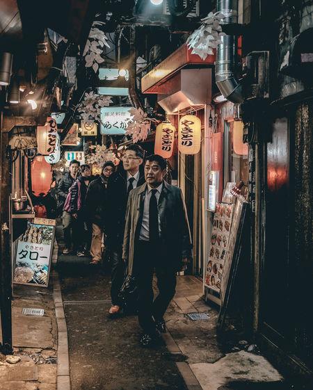 People walking on illuminated street market at night