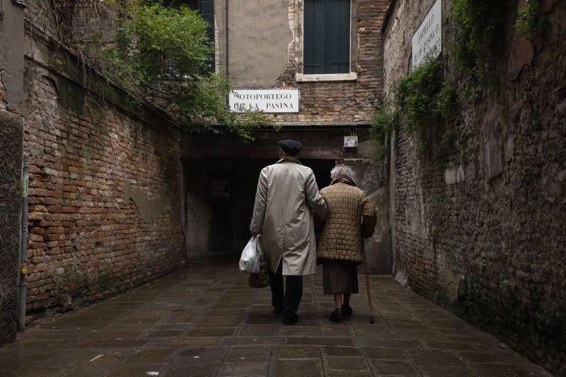 Rear view of couple walking along buildings