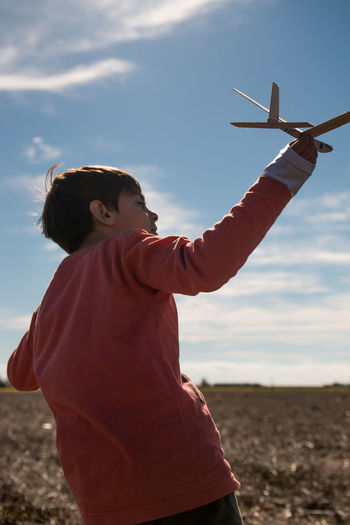 Rear view of boy playing with model airplane on land against sky