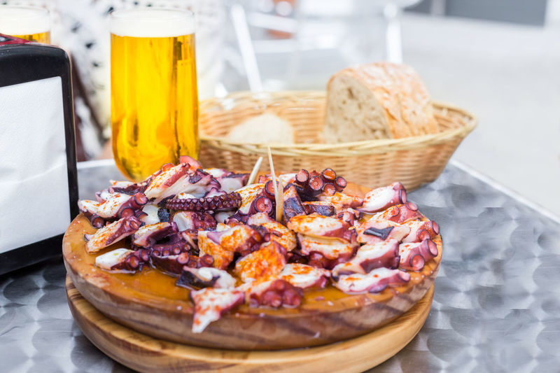 Cold beer and Wooden plate of galician style cooked octopus with paprika and olive oil. Pulpo a la gallega Beer Cooked Food Cuisine Dish Galicia Pulpo A La Gallega Seafood Spanish Food Tapas Cooked Fish Food Fresh Galician Galician Food Gastronomy Gourmet Octopus Olive Oil Paprika Plate Pulpo A Feira Tasty Traditional Typical Food