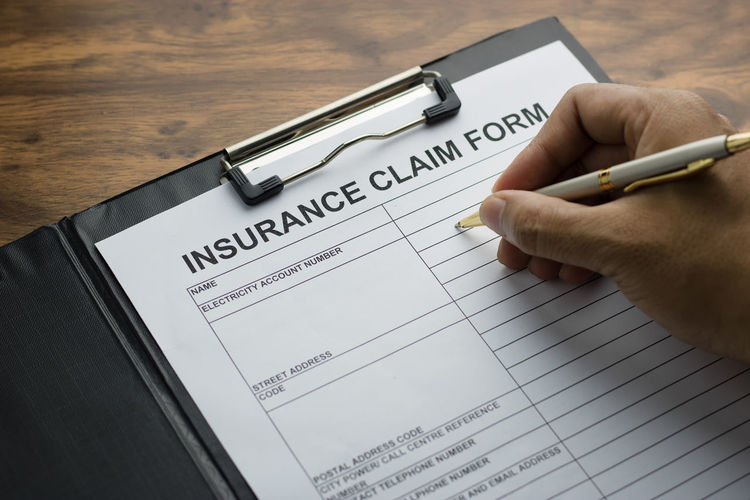 Cropped hand writing on insurance paper