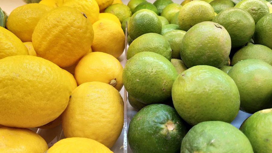 Full frame shot of limes and lemons for sale at market