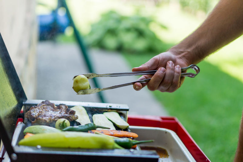 Cropped image of hand holding barbeque vegetable with tongs