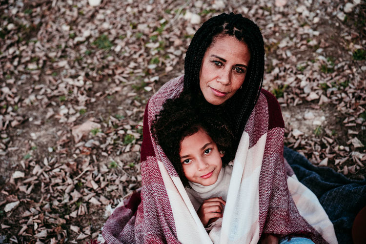 Portrait of smiling daughter sitting with mother on land