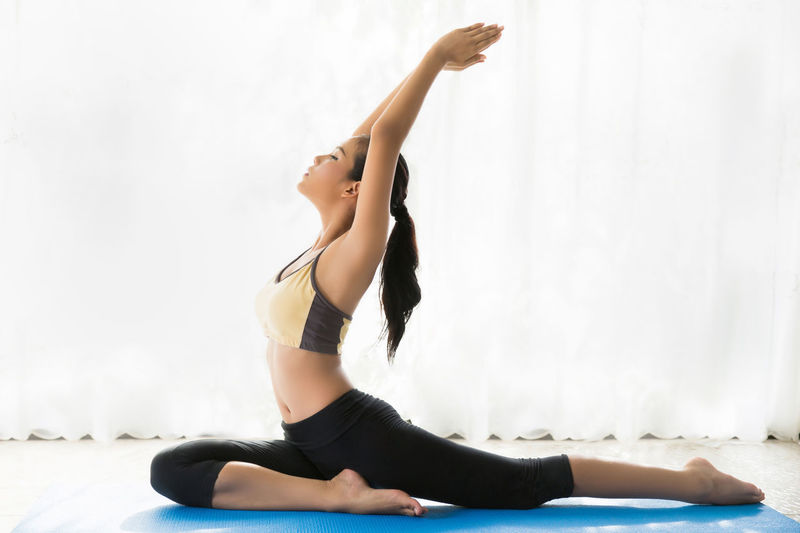 Side view of young woman arms raised practicing yoga against curtain at home