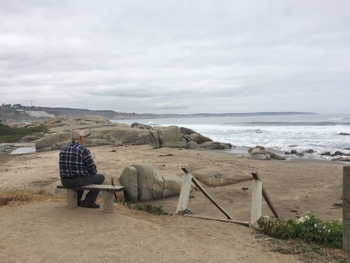 Rear View Of Man Sitting On Bench While Looking At Sea Against Sky