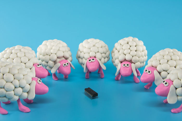 White polymer clay sheep gather around an electronic chip on a blue background. White sheep in this photo represent the society and the way it accepts something new and different. The sheep, considered to be dumb, are seen inspecting an advanced electronic chip, though it's clear they don't have a clue what they are looking at. It's like presenting a gun to a bunch of primitive cavemen. Same way, offering a technological device to a group of sheep. Useless and overwhelming. Cattle Cautious Chip Clueless Computers Confused Curious Cute Dumb  Electronics  Equipment Flock Funny High-tech Industry Irrelevant Mysterious Research Ridiculous Science Technical Technology Unusable Useless White