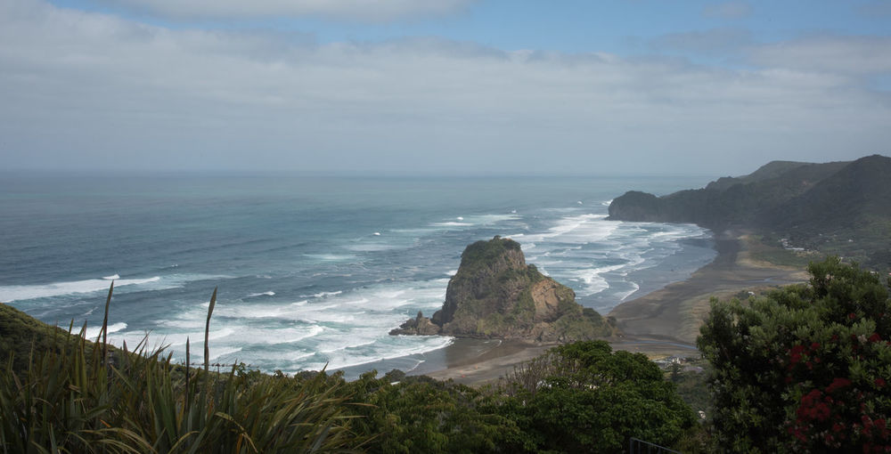 Elevated view over the volcanic black sand Piha Beach with Lion Rock and powerful Tasman Sea waves on an overcast day in Auckland, New Zealand Auckland Coastline Flowing Water Lion Rock Piha Beach Rock Formation Wave Beach Beauty In Nature Black High Angle View Horizon Over Water Landscape Motion Nature New Zealand Piha Power In Nature Rock - Object Sand Scenics - Nature Sea Tide Volcanic Landscape Water