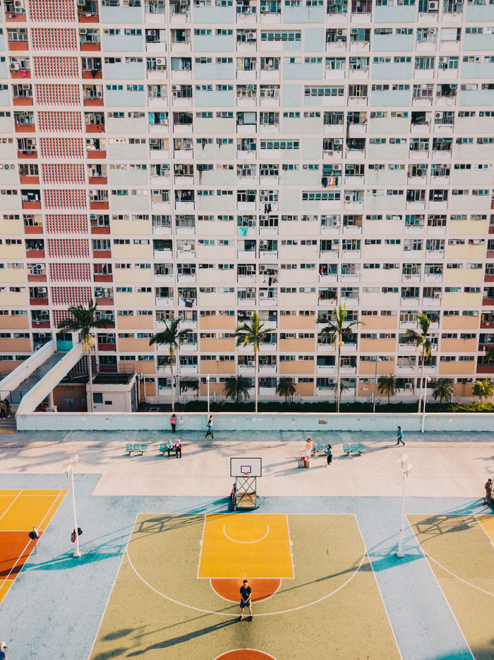 HIGH ANGLE VIEW OF PEOPLE IN SWIMMING POOL AGAINST BUILDINGS