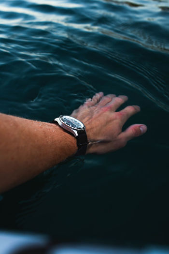 Cropped hand of man touching sea