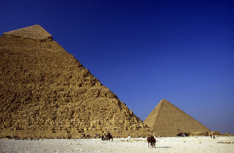 People on desert landscape against pyramids and sky