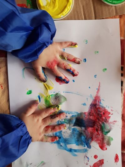 Cropped hand of child drawing at table