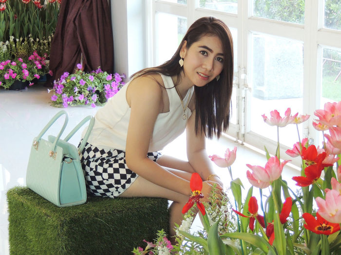 Portrait of beautiful woman sitting by flowering plants at home