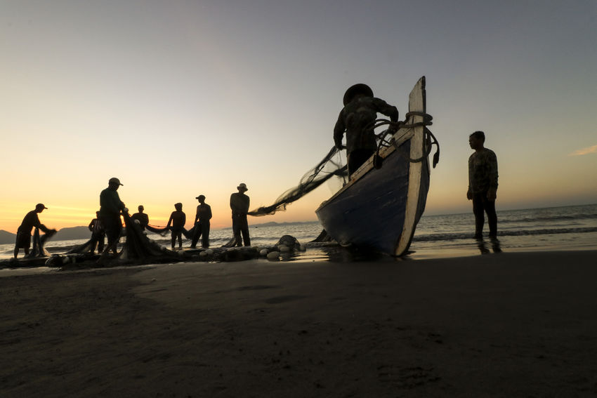 the coastal fishermen Gampong Jawa Banda Aceh are doing activities pulling pukat (fishing nets) on the coast as an afternoon activity as a livelihood of local residents. Aceh Economics Silhouette Work Activity Coast Daylife Fisher Fisherman Fishing Livelihood Nets Sunset Sunsetsilhouettes