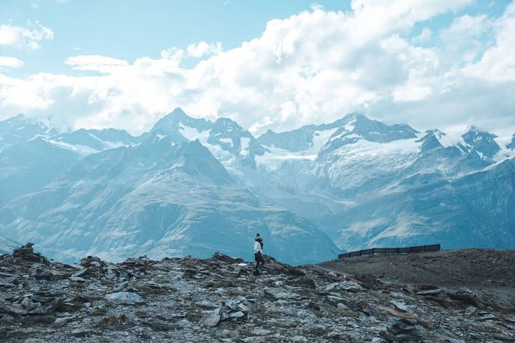 Rear view of man standing on snowcapped mountains against sky