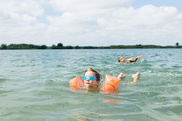 Boys swimming in sea against sky