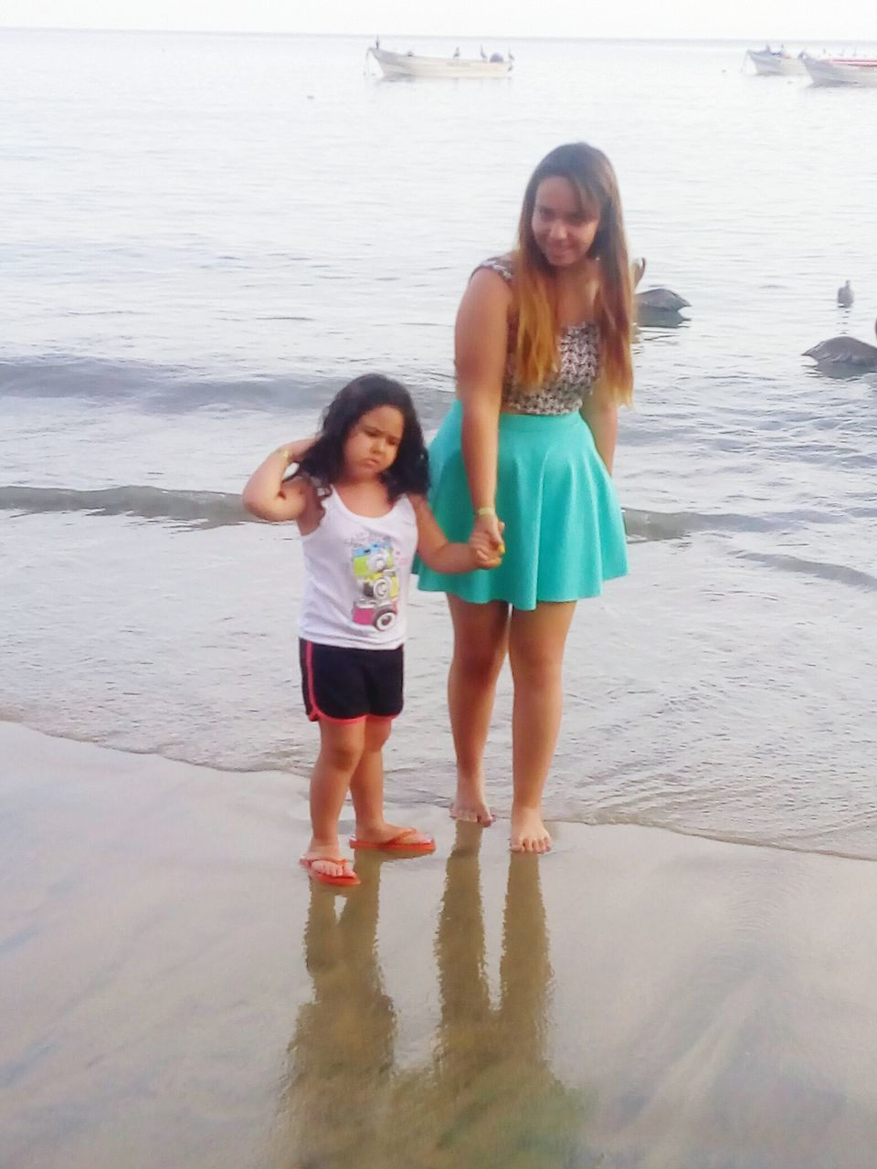 two people, full length, looking at camera, leisure activity, beach, young women, young adult, standing, front view, real people, sea, togetherness, water, vacations, day, casual clothing, portrait, smiling, outdoors, happiness, sand, lifestyles, nature, bonding, girls, childhood, beautiful woman, sky
