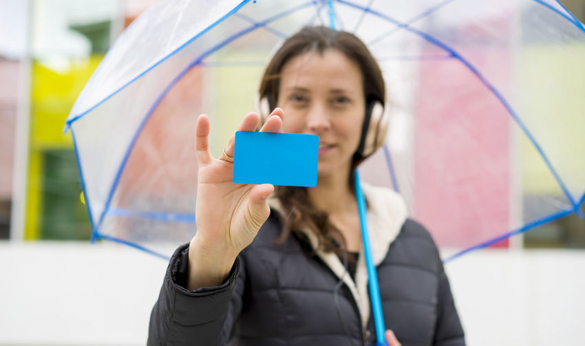 Woman Showing Business Card While Holding Umbrella