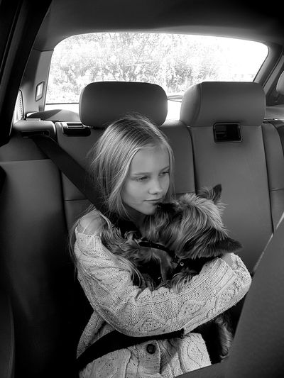 Thoughtful girl holding dog while traveling in car
