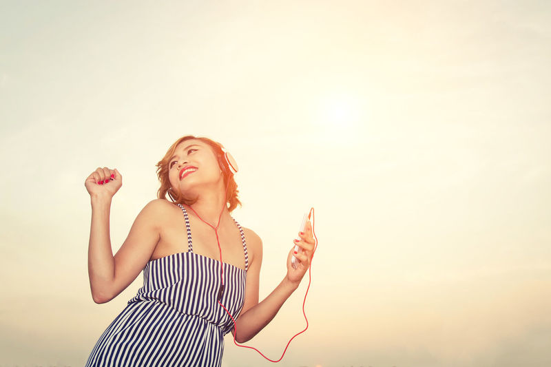Low Angle View Of Woman Listening Music