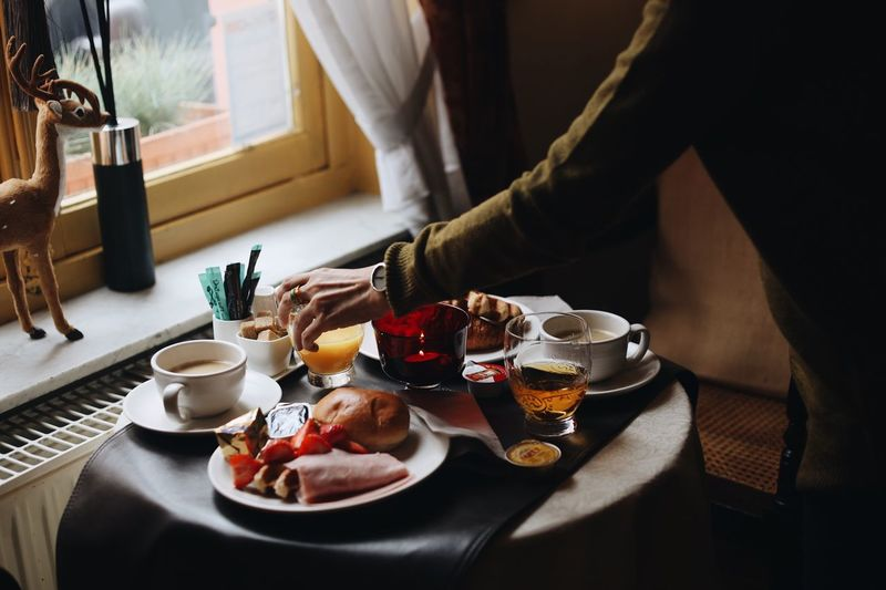 Midsection of person eating breakfast on table
