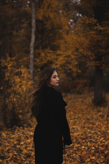 Rear view of beautiful young woman standing in forest during autumn
