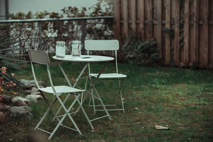 Empty chairs and table in lawn