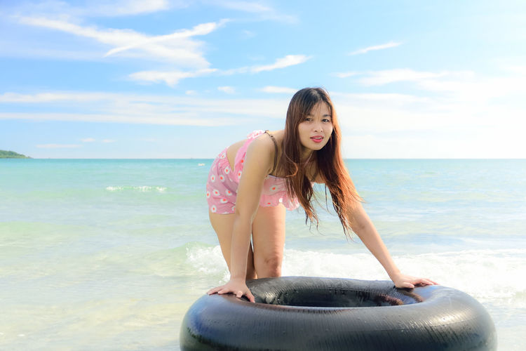 Portrait of beautiful woman leaning on inflatable ring in sea against sky