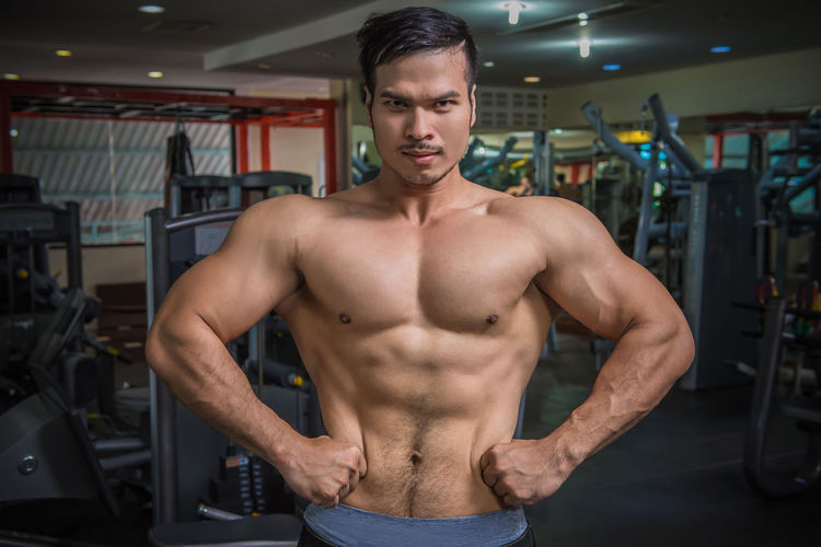 Adult Athlete Exercising Front View Gym Healthy Lifestyle Human Muscle Indoors  Lifestyles Men Muscular Build One Person Real People Shirtless Sport Sports Training Standing Strength Vitality Weight Training  Wellbeing