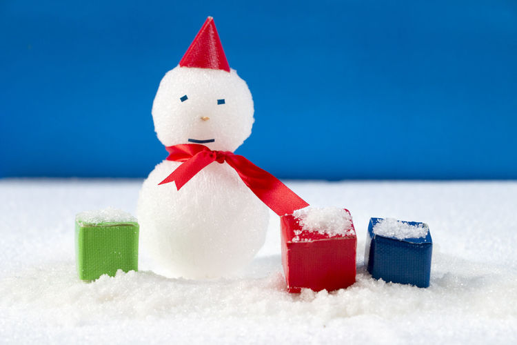 Close-up of christmas decorations on snow against blue background