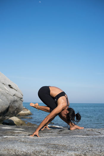 Young Woman Exercising At Beach Against Sky