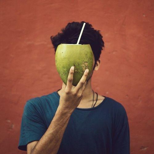 Close-up of man holding fruit against orange wall