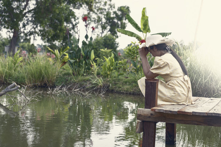 Side view of man sitting by plants against lake
