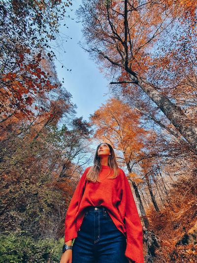 Portrait of young woman standing by trees during autumn