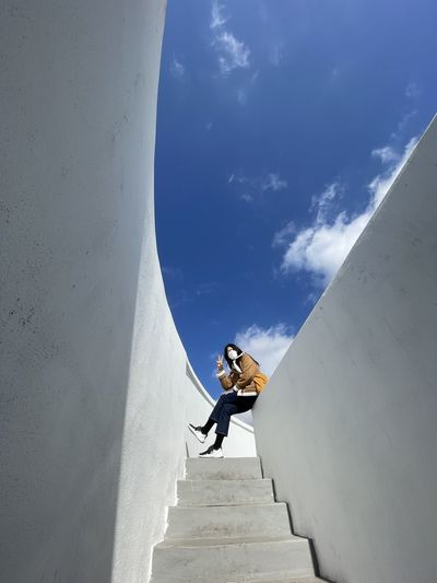 Low angle view of woman climbing on wall against sky