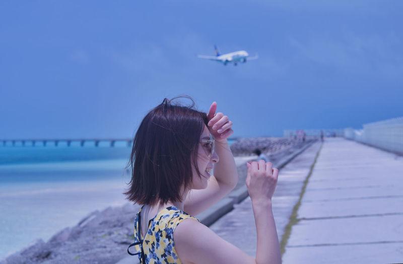 Portrait of woman against blue sea against sky