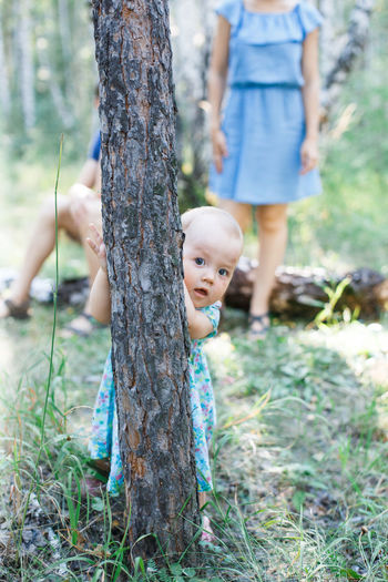 EyeEmNewHere Casual Clothing Childhood Day Eye4photography  Field Focus On Foreground Forest Girl Grass Growth Leisure Activity Low Section Nature Outdoors People Real People Togetherness Tree Tree Trunk