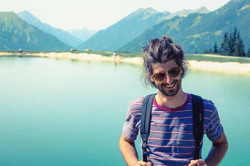 man with sunglasses at a mountain lake in summer Happy People Bun Manbun Beard Sunglasses Young Adult Water Happiness Smiling Mountain Nature Lake One Person Vacations Young Men Outdoors Real People Portrait Summer Only Men Cheerful Day Beauty In Nature An Eye For Travel