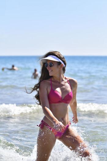 Woman wearing sunglasses walking in sea against clear sky