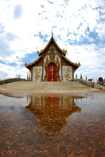 Buddhist temple reflecting on puddle against cloudy sky